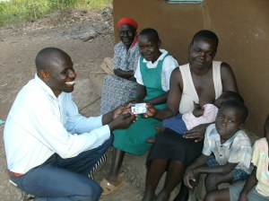 Amelia receives her hospital insurance card from Nicholas Odwar, Luo Care's administrator.